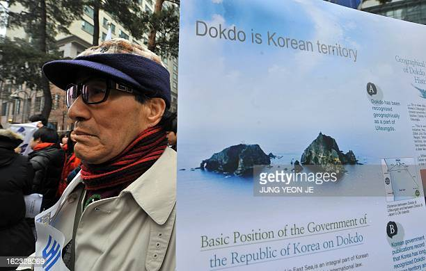 A South Korean protestor stands next to a placard reading 'Dokdo is Korean territory' during an antiJapan rally outside the Japanese embassy in Seoul...