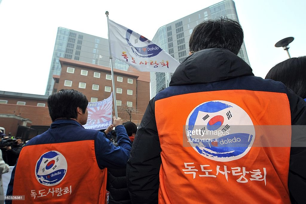 A South Korean protestor (L) waves a flag reading 'I love Dokdo' during an anti-Japan rally outside the Japanese embassy in Seoul on February 22, 2013 denouncing Japan's claims to the tiny chain of Seoul-controlled rocky islands, known as Dokdo in Korea and Takeshima in Japan. South Korea bashed Japan on February 22 for holding an annual rally to renew its claim to a set of tiny islands controlled by South Korea, which has been at the centre of a long-standing territorial feud.