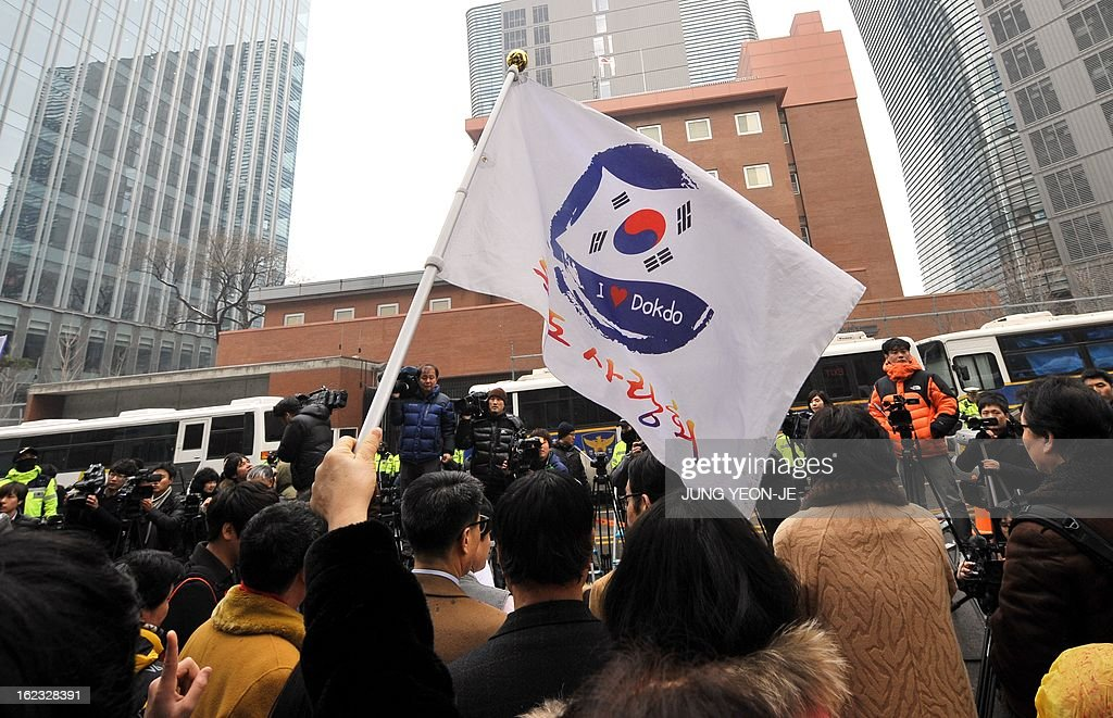 A South Korean protestor waves a flag reading 'I love Dokdo' during an anti-Japan rally outside the Japanese embassy in Seoul on February 22, 2013 denouncing Japan's claims to the tiny chain of Seoul-controlled rocky islands, known as Dokdo in Korea and Takeshima in Japan. South Korea bashed Japan on February 22 for holding an annual rally to renew its claim to a set of tiny islands controlled by South Korea, which has been at the centre of a long-standing territorial feud.