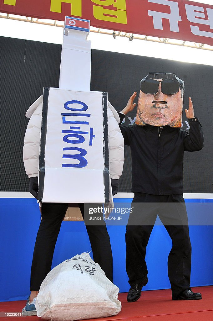 A South Korean protestor (R) wearing a mask of North Korean leader Kim Jong-Un dances next to a mock North Korean rocket (L) during a rally denouncing North Korea's nuclear test, in Seoul on February 22, 2013. The United States and South Korea on February 21 announced plans for major annual joint military exercises as regional tensions run high following North Korea's third nuclear test.