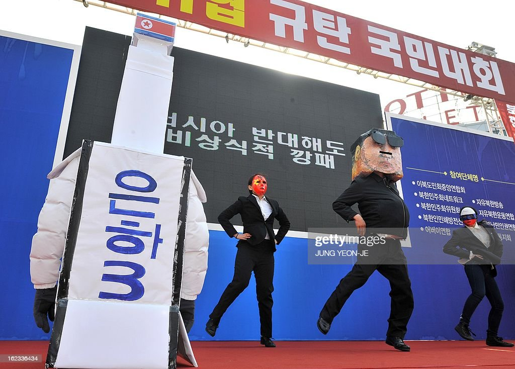 A South Korean protestor (2nd R) wearing a mask of North Korean leader Kim Jong-Un dances next to a mock North Korean rocket (L) during a rally denouncing North Korea's nuclear test, in Seoul on February 22, 2013. The United States and South Korea on February 21 announced plans for major annual joint military exercises as regional tensions run high following North Korea's third nuclear test.