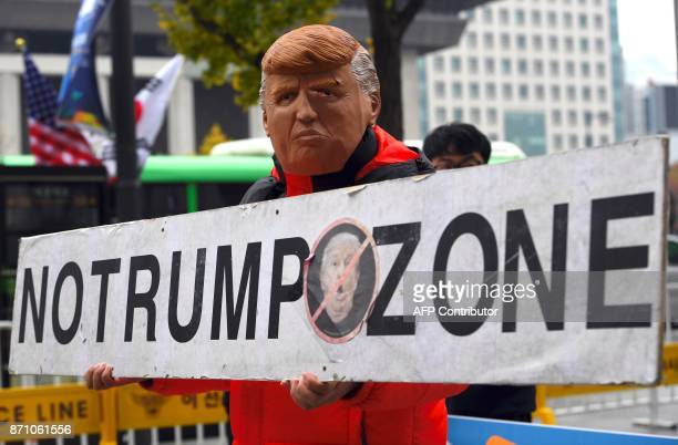 A South Korean protestor wearing a mask of US President Donald Trump holds a banner reading 'No Trump Zone' during an antiUS rally near the US...