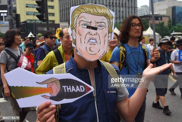 A South Korean protestor wearing a mask of US President Donald Trump marches toward the US embassy during a rally against the deployment of the US...