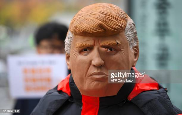 A South Korean protestor wears a mask of US President Donald Trump during an antiUS rally near the US embassy in Seoul on November 7 2017 ahead of US...