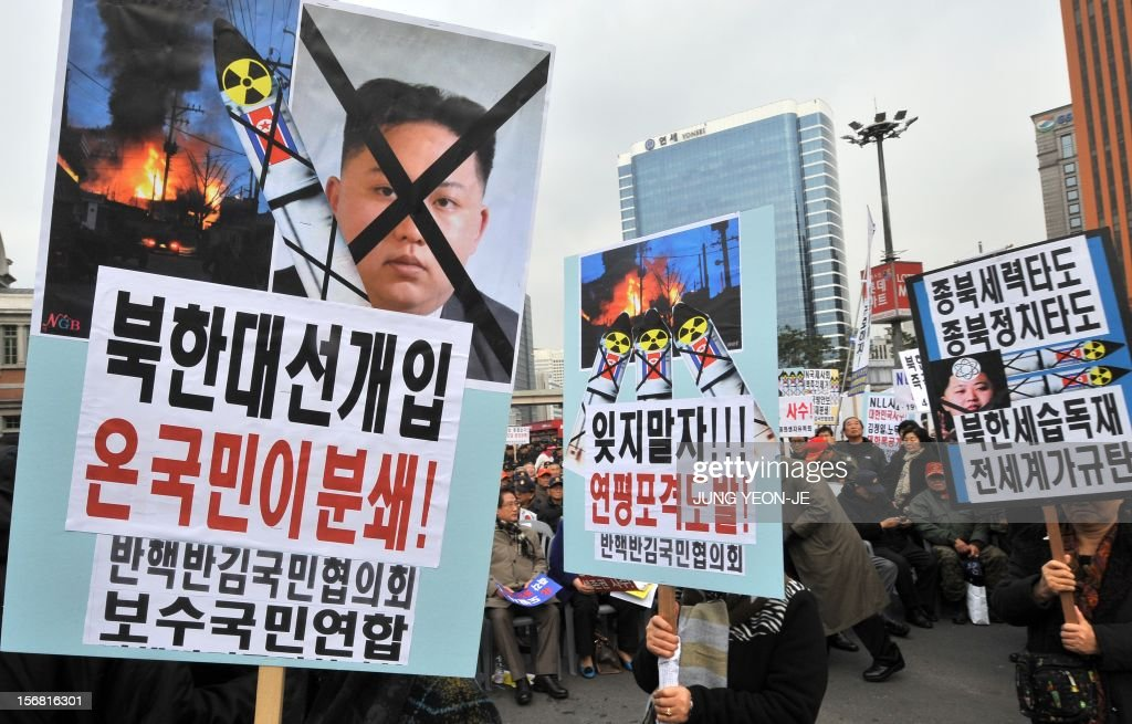 South Korean protestors carry placards showing a portrait of North Korean leader Kim Jong-Un (L) during an anti-Pyongyang rally in Seoul on November 22, 2012, one day before the second anniversary of the shelling on Yeonpyeong island near the disputed Yellow Sea border. North Korea has threatened to repeat its 2010 artillery attack on a border island, as South Korea prepares to mark on November 23 the second anniversary of the shelling that left four dead.