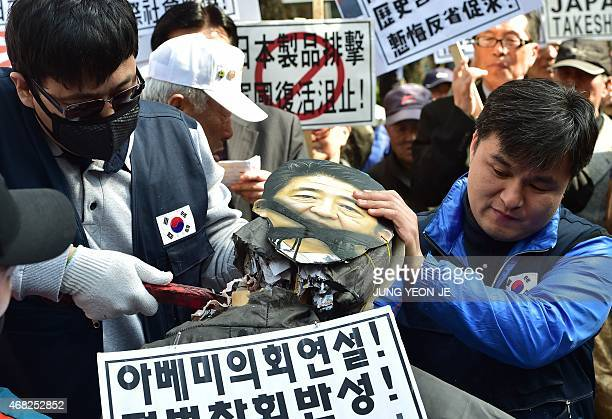South Korean protestors cut an effigy of Japan's Prime Minister Shinzo Abe with a saw during an antiJapan rally outside the Japanese embassy in Seoul...