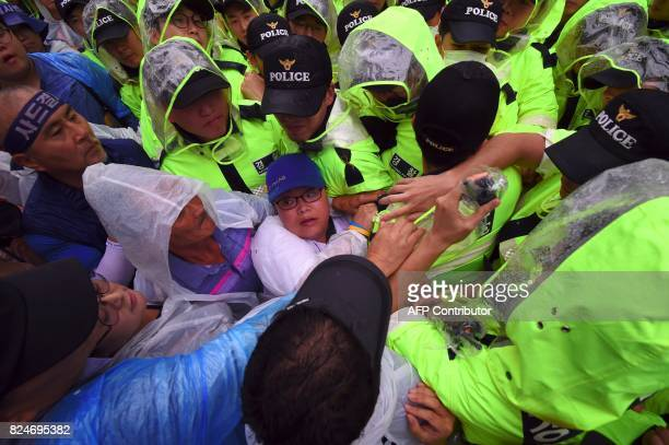 South Korean protestors grapple with police as they march toward the presidential house during a rally against the deployment of the US Terminal High...