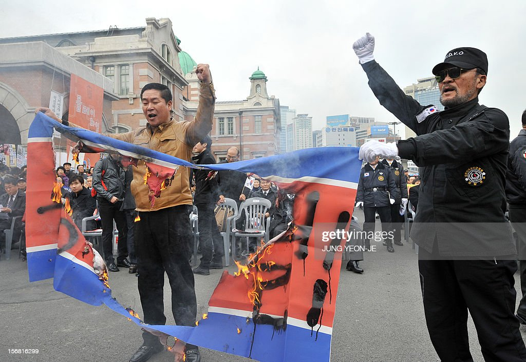 South Korean protestors hold a burning North Korean flag during an anti-Pyongyang rally in Seoul on November 22, 2012, one day before the second anniversary of the shelling on Yeonpyeong island near the disputed Yellow Sea border. North Korea has threatened to repeat its 2010 artillery attack on a border island, as South Korea prepares to mark on November 23 the second anniversary of the shelling that left four dead. AFP PHOTO / JUNG YEON-JE