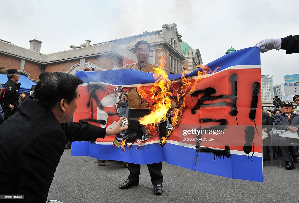 South Korean protestors hold a burning North Korean flag during an anti-Pyongyang rally in Seoul on November 22, 2012, one day before the second anniversary of the shelling on Yeonpyeong island near the disputed Yellow Sea border. North Korea has threatened to repeat its 2010 artillery attack on a border island, as South Korea prepares to mark on November 23 the second anniversary of the shelling that left four dead.
