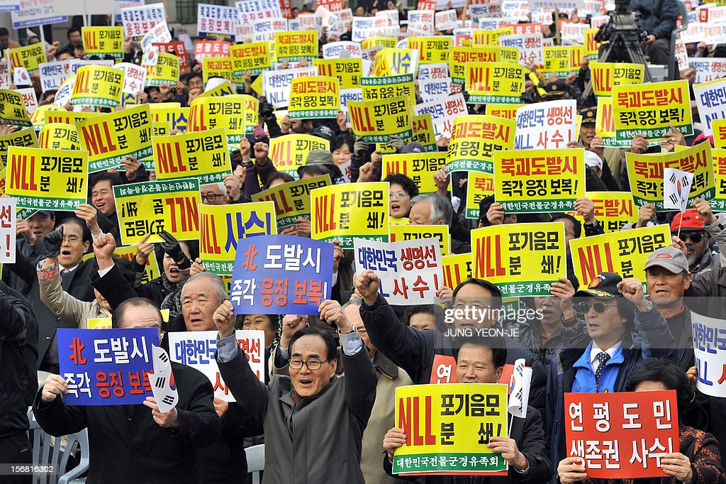 South Korean protestors hold placards reading 'Punish against North Korea's provocation!' during an anti-Pyongyang rally in Seoul on November 22, 2012, one day before the second anniversary of the shelling on Yeonpyeong island near the disputed Yellow Sea border. North Korea has threatened to repeat its 2010 artillery attack on a border island, as South Korea prepares to mark on November 23 the second anniversary of the shelling that left four dead. AFP PHOTO / JUNG YEON-JE