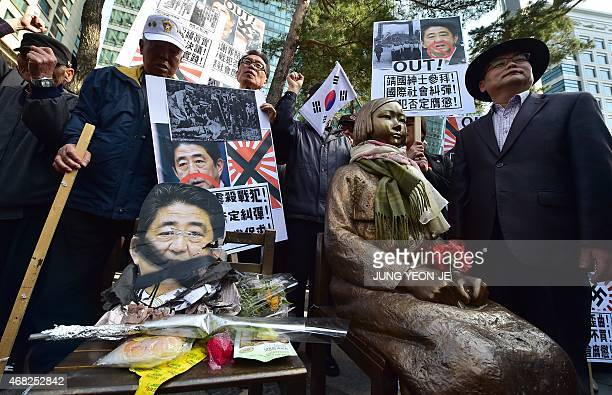 South Korean protestors place a damaged portrait of Japan's Prime Minister Shinzo Abe next to a statue of a South Korean teenage girl in traditional...