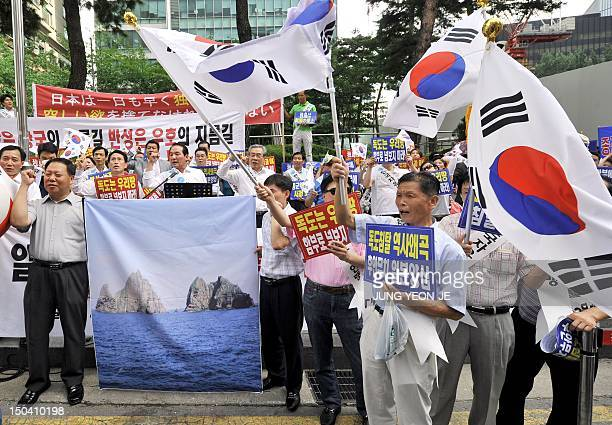 South Korean protestors wave the national flags during a rally in front of the Japanese embassy in Seoul on August 17 2012 denouncing Japan's claims...