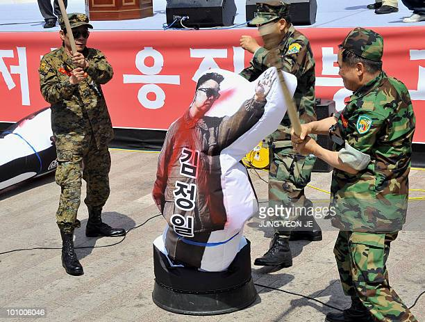 South Korean protestors wield sticks at a humansized balloon painted with North Korean leader Kim JongIl during a rally against North Korea for the...