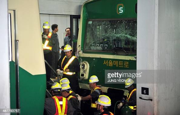 South Korean railway workers inspect two damaged trains after they collided at Sangwangsimni station in Seoul on May 2 2014 Two subway trains...