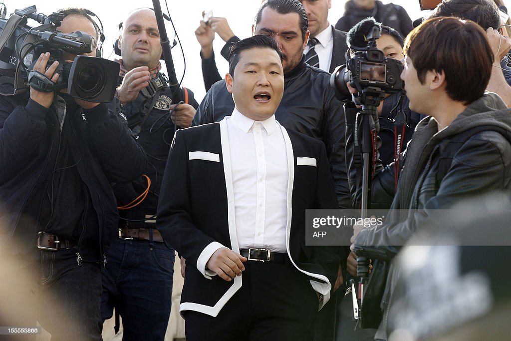 South Korean rapper Park Jae-Sang also known as Psy (C) leaves after performing 'Gangnam Style' in front of a crowd during a flashmob on November 5, 2012 in Paris. The video to 'Gangnam Style' went viral after its July release, becoming the second most viewed clip in YouTube history, where it has notched up more than 650 million hits despite being sung almost entirely in Korean.