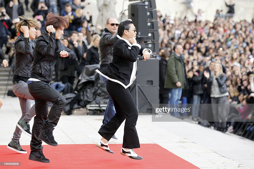 South Korean rapper Park Jae-Sang also known as Psy performs 'Gangnam Style' in front of a crowd during a flashmob on November 5, 2012 in Paris. The video to 'Gangnam Style' went viral after its July release, becoming the second most viewed clip in YouTube history, where it has notched up more than 650 million hits despite being sung almost entirely in Korean. AFP PHOTO / THOMAS SAMSON