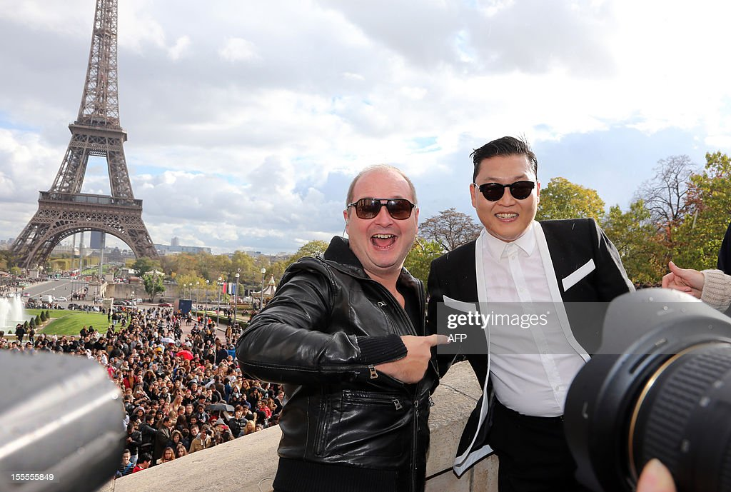 South Korean rapper Park Jae-Sang also known as Psy poses with tv anchor Sebastien Cauet (L) before performing 'Gangnam Style' in front of a crowd during a flashmob on November 5, 2012 in Paris. The video to 'Gangnam Style' went viral after its July release, becoming the second most viewed clip in YouTube history, where it has notched up more than 650 million hits despite being sung almost entirely in Korean.