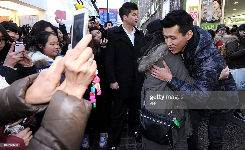 South Korean rapper Sean (R) holds a 'Free Hug' event at a shopping district in central Seoul on January 27, 2013. Sean promised to hold the event if his wife's movie 'Man on the Edge' hit three million attended. REPUBLIC OF KOREA OUT JAPAN OUT AFP PHOTO / Starnews