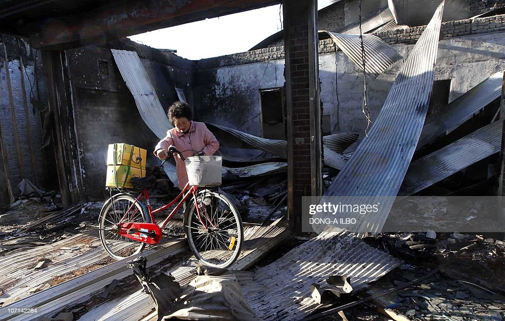 A South Korean resident pulls a bicycle along the wreckage of houses destroyed by North Korea's artillery shelling on Yeonpyeong island in the...