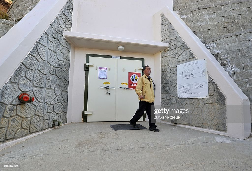 South Korean resident walks past a gate of an air-raid shelter at the South Korea-controlled island of Yeonpyeong near the disputed waters of the Yellow Sea on April 12, 2013. South Korea's defence ministry said on April 12 it doubted North Korea had the ability to launch a nuclear-armed ballistic missile as claimed in a report by the US military spy agency.