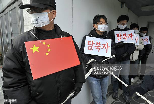 South Korean rights activists perform role of mock Chinese police and North Korean refugee outside the Chinese embaasy in Seoul on February 21 2012...