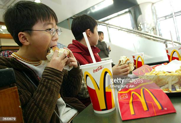 South Korean school boys eat hamburgers at McDonalds December 28 2003 in Seoul South Korea South Korea has banned imports of US beef and beef...
