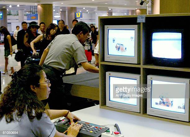 South Korean security member checks luggage of travelers through Xray monitors in Incheon International Airport west of Seoul 12 July 2004 Security...