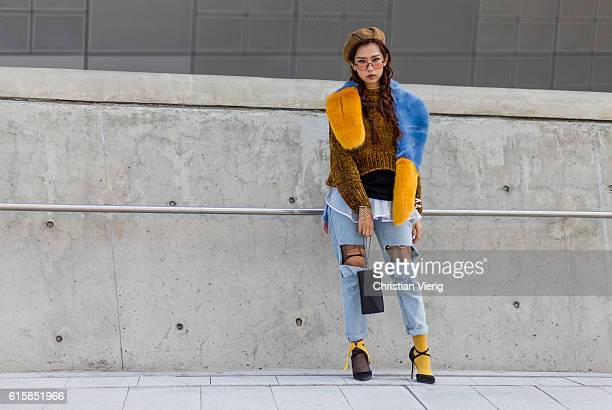 South Korean singer Min Nguyen Minh Hang wearing a ripped denim jeans heels yellow socks fur scarf wool sweater on October 20 2016 in Seoul South...