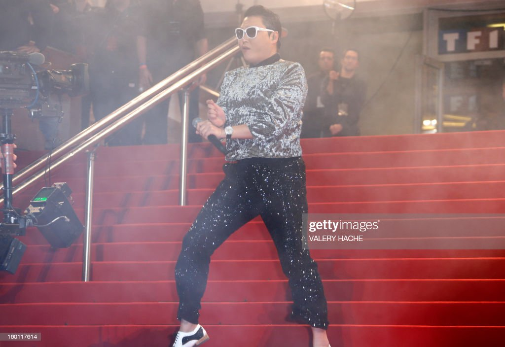 South korean singer Psy dances on the red carpet upon arrival at the Palais des Festivals during the 14th Annual NRJ Music Awards on January 26, 2013 in Cannes, southeastern France. News that the global music industry has finally turned the corner and is on the road to recovery should help get the annual four-day gathering of many of the world's top music execs at the MIDEM trade fair that opens here Saturday off to a good start. AFP PHOTO / VALERY HACHE