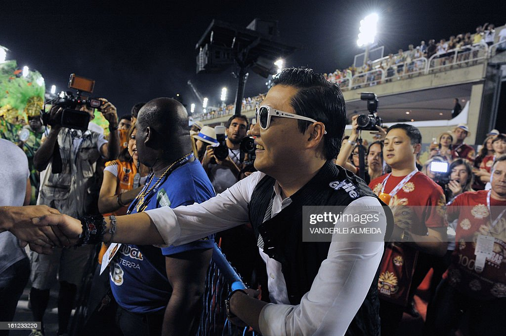 South Korean singer Psy (R) shakes hands with a fan at the Sambadrome in Rio de Janeiro, Brazil on February 9, 2013. The creator of the song 'Gangnam style' is in Rio on a two-day visit to enjoy carnival.