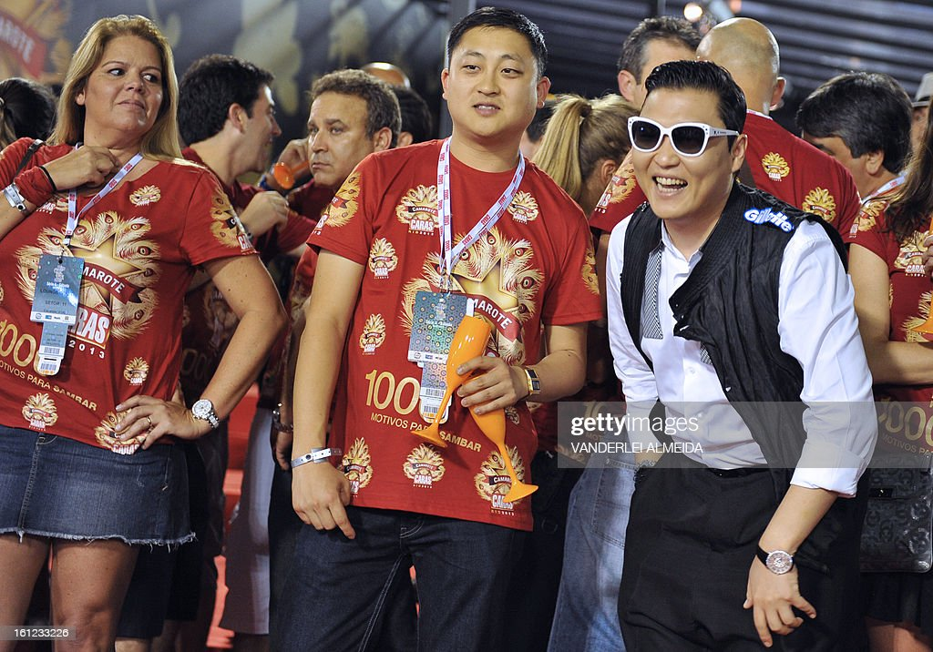 South Korean singer Psy (R) smiles at the Sambadrome in Rio de Janeiro, Brazil on February 9, 2013. The creator of the song 'Gangnam style' is in Rio on a two-day visit to enjoy carnival. AFP PHOTO/VANDERLEI ALMEIDA
