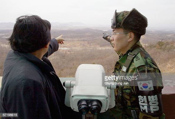 South Korean soldier and a tourist look in the direction of North Korea near the demilitarized zone at the Dora Observation Post on February 15 2005...