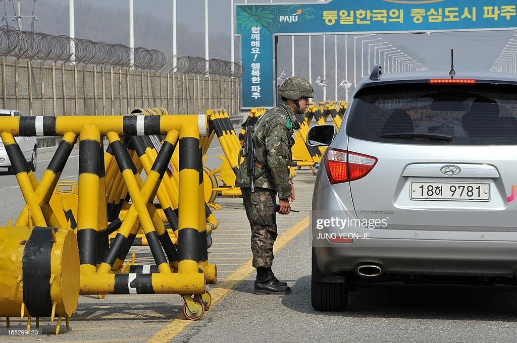 A South Korean soldier checks a car on the road linked to North Korea at a military check point in Paju near the demilitarized zone (DMZ) dividing the two Koreas on April 3, 2013. North Korea on April 3 delayed the entry of South Koreans to a joint industrial complex in a rare move amid high tensions on the Korean peninsula, the South's Unification Ministry said.