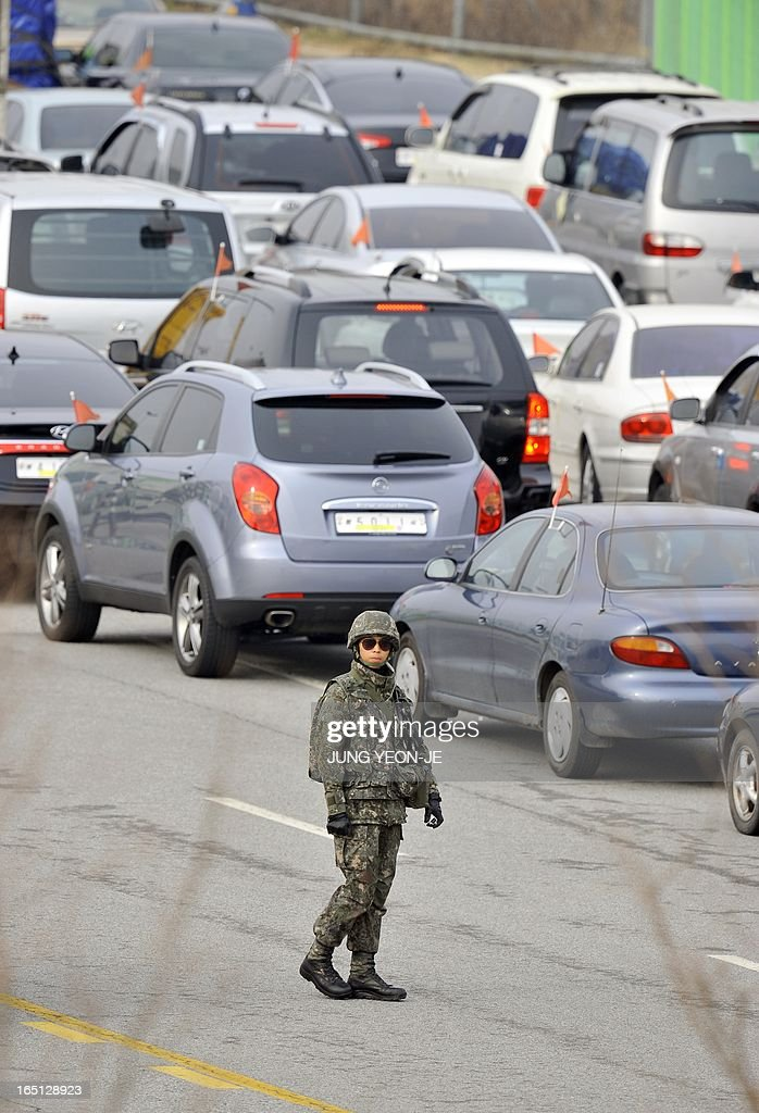 A South Korean soldier checks vehicles leaving for North Korea at a military check point of the inter-Korean transit office in Paju near the Demilitarized Zone (DMZ) on April 1, 2013. South Korean workers and cargo on April 1 headed for the Kaesong Industrial Complex without a hitch despite North Korea's recent threat to close the joint industrial zone in the communist country. AFP PHOTO / JUNG YEON-JE