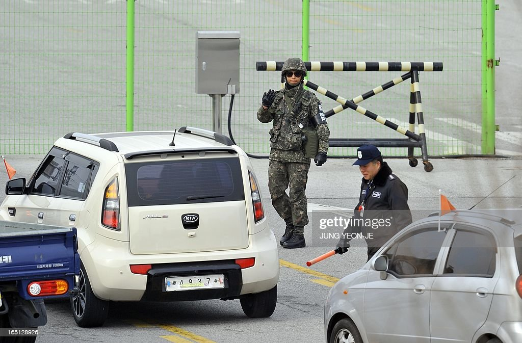 A South Korean soldier (C) checks vehicles leaving for North Korea at a military check point of the inter-Korean transit office in Paju near the Demilitarized Zone (DMZ) on April 1, 2013. South Korean workers and cargo on April 1 headed for the Kaesong Industrial Complex without a hitch despite North Korea's recent threat to close the joint industrial zone in the communist country.