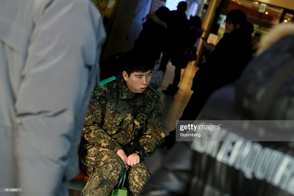A South Korean soldier looks at a television screen showing a news broadcast on North Korea's nuclear test at Seoul Station in Seoul, South Korea, on Tuesday, Feb. 12, 2013. North Korea conducted its third underground nuclear test today, underscoring a disregard for an international community that has already isolated the totalitarian state from the global economy. Photographer: SeongJoon Cho/Bloomberg via Getty Images