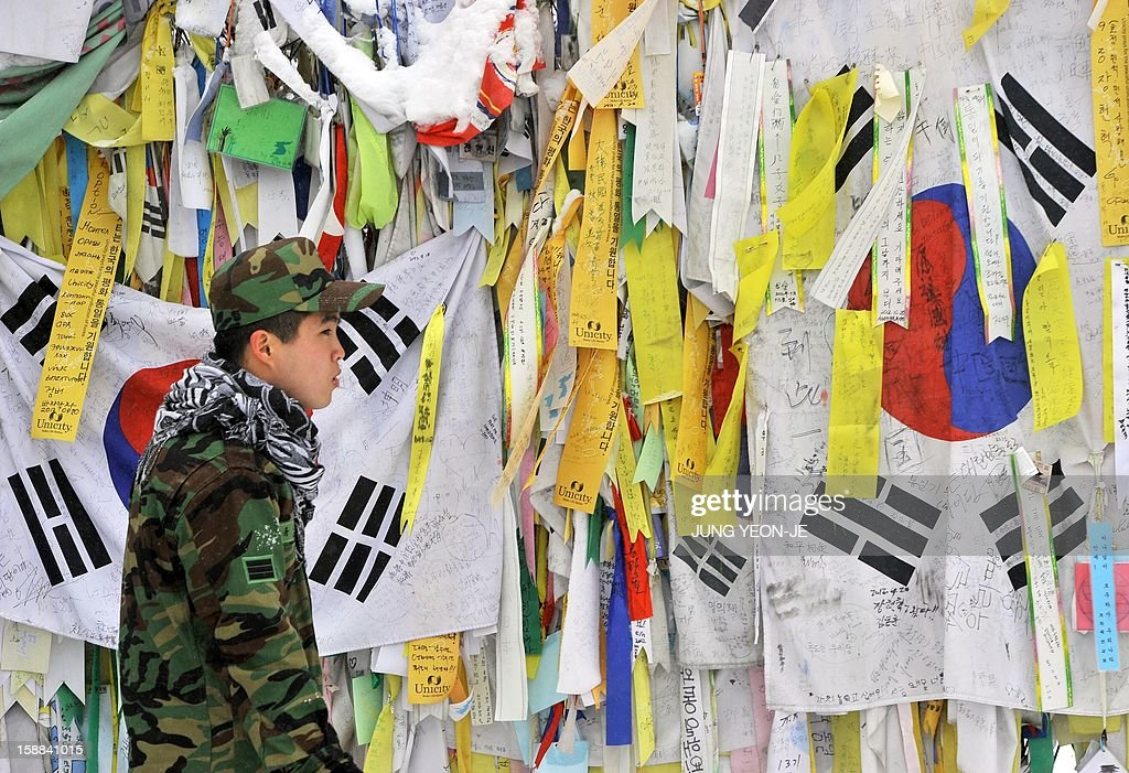 A South Korean soldier looks at 'reunification ribbons' displayed on a military barbed wire fence at Imjingak peace park in Paju near the Demilitarized Zone (DMZ) dividing the two Koreas on January 1, 2013. North Korean leader Kim Jong-Un called on January 1, 2013 for an easing of tensions with the South and flagged a 'radical turnabout' in the national economy in a rare voiced message broadcast on state television. AFP PHOTO / JUNG YEON-JE
