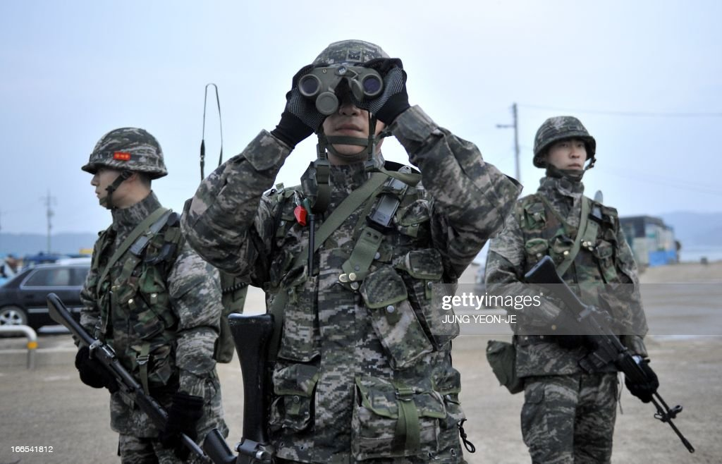 A South Korean soldier looks through binoculars as they patrol on the South Koreacontrolled island of Yeonpyeong near the disputed waters of the...