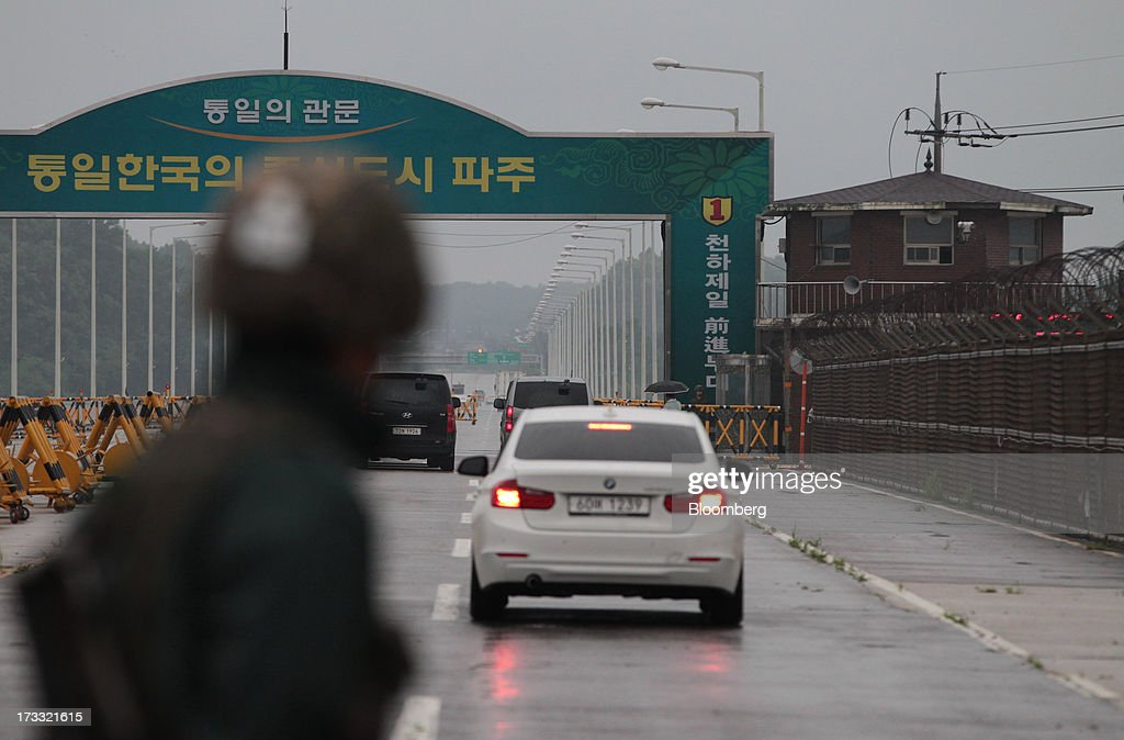 A South Korean soldier looks toward a military check point on the Unification Bridge, linked to North Korea, near the demilitarized zone (DMZ) in Paju, South Korea, on Friday, July 12, 2013. North Korea notified South Korea today that it has deferred two separate sets of talks on the tours and the family reunions it proposed yesterday, and said it wants to focus on the ongoing dialog to reopen the joint Gaeseong industrial zone, the Souths Unification Ministry said in an e-mailed statement. The two sides yesterday decided to hold talks in Gaeseong on July 15, which will be their third round in one week, on normalizing operations in Gaeseong after the North unilaterally recalled its workers in April. Photographer: SeongJoon Cho/Bloomberg via Getty Images