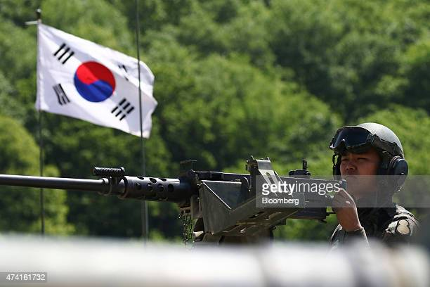A South Korean soldier of the 8th Mechanized Infantry Division mans a machine gun atop a battle tank as a South Korean flag flies nearby during a...