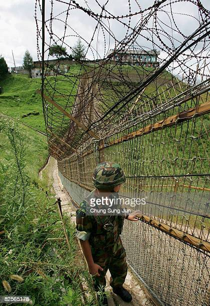 South Korean soldier patrols a barbedwire fence on the demilitarized zone separating North Korea from South Korea on August 27 2008 in the...
