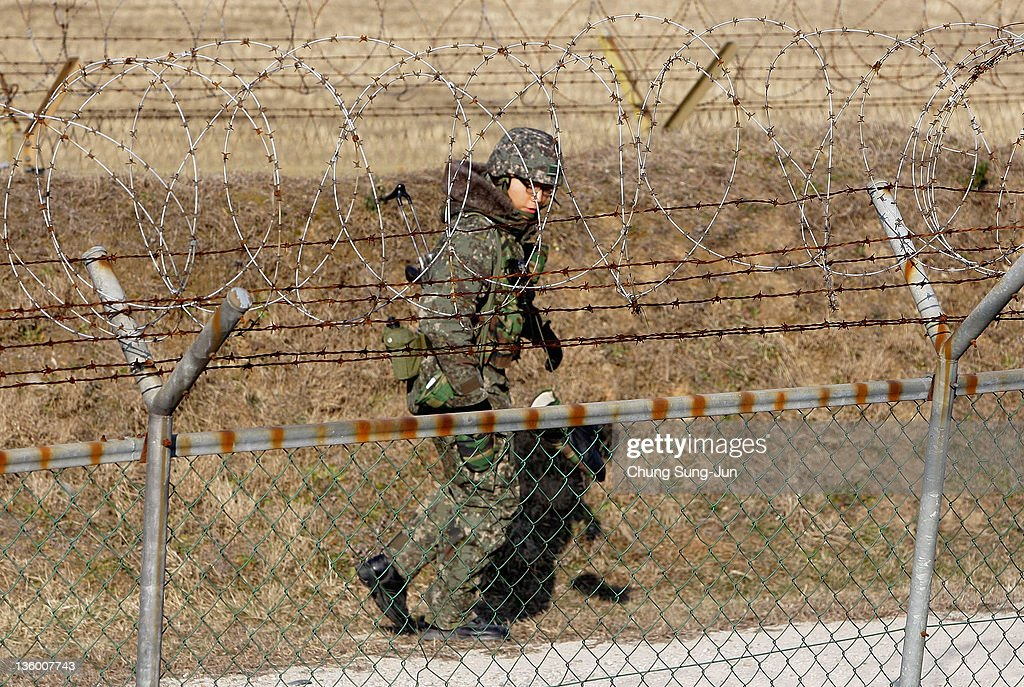 South Korean soldier patrols inside the barbedwire fence at Imjinkak near the Demilitarized zone separating South and North Korea on December 20 2011...