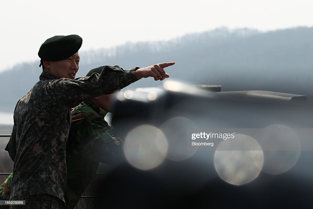 A South Korean soldier points towards the north side of the border at the Imjingak pavilion near the demilitarized zone (DMZ) in Paju, South Korea, on Wednesday, April 3, 2013. North Korea prevented South Korean workers from entering a jointly run industrial park today, adding to tensions after saying it will restart a mothballed nuclear plant and threatening to attack its southern neighbor. Photographer: SeongJoon Cho/Bloomberg via Getty Images