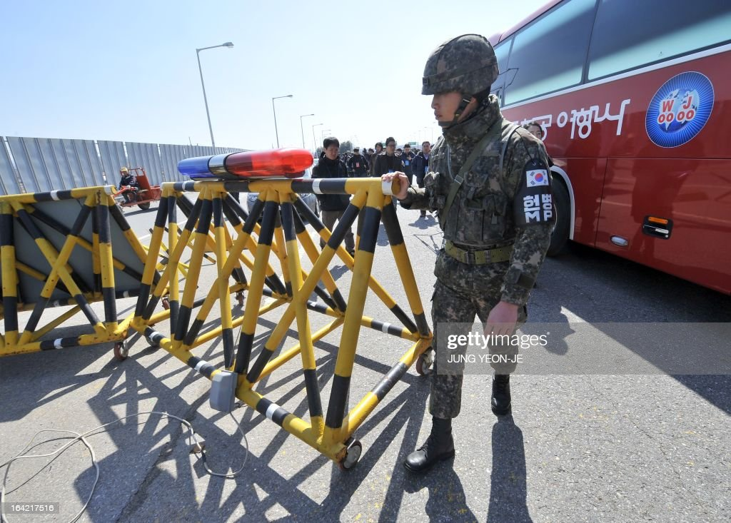 A South Korean soldier removes a barricade as children march on the road linked to North Korea at a military check point in Paju near the Demilitarized Zone (DMZ) dividing the two Koreas on March 21, 2013 during a campaign for a peace forest on the tense inter-Korean border. Sixteen-year-old Korean-American Jonathan Lee, an environmental and peace activist, spearheaded this campaign and wanted the international community to agree to have children from both sides meet and create a Children's Peace Park in the DMZ.