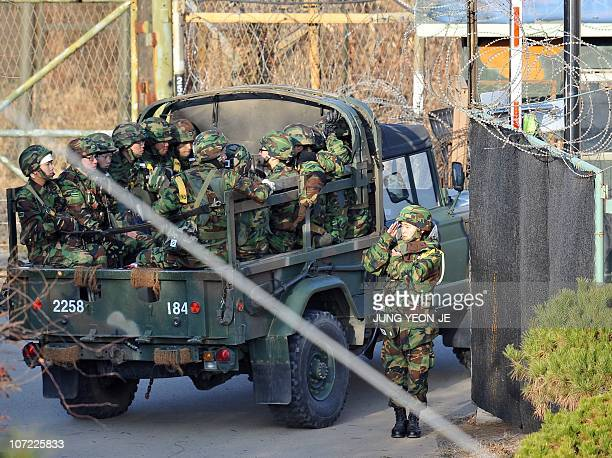 A South Korean soldier salutes as a military truck drives past at a gate of a military guard area in Paju near the Demilitarized Zone separating...