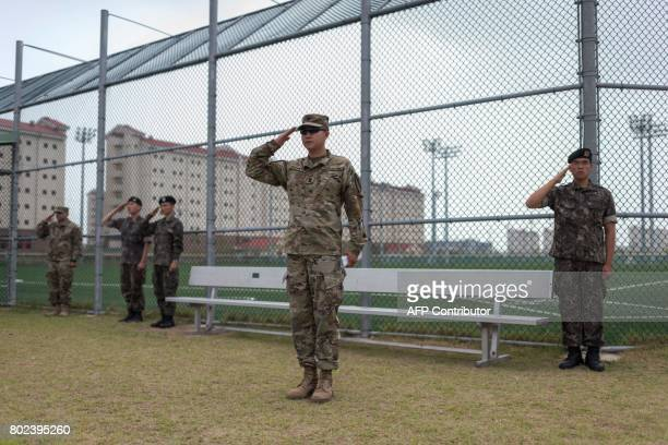 A South Korean soldier salutes as US soldiers of the 1st Armoured Brigade Combat Team 1st Infantry Division salute during a transfer of authority...