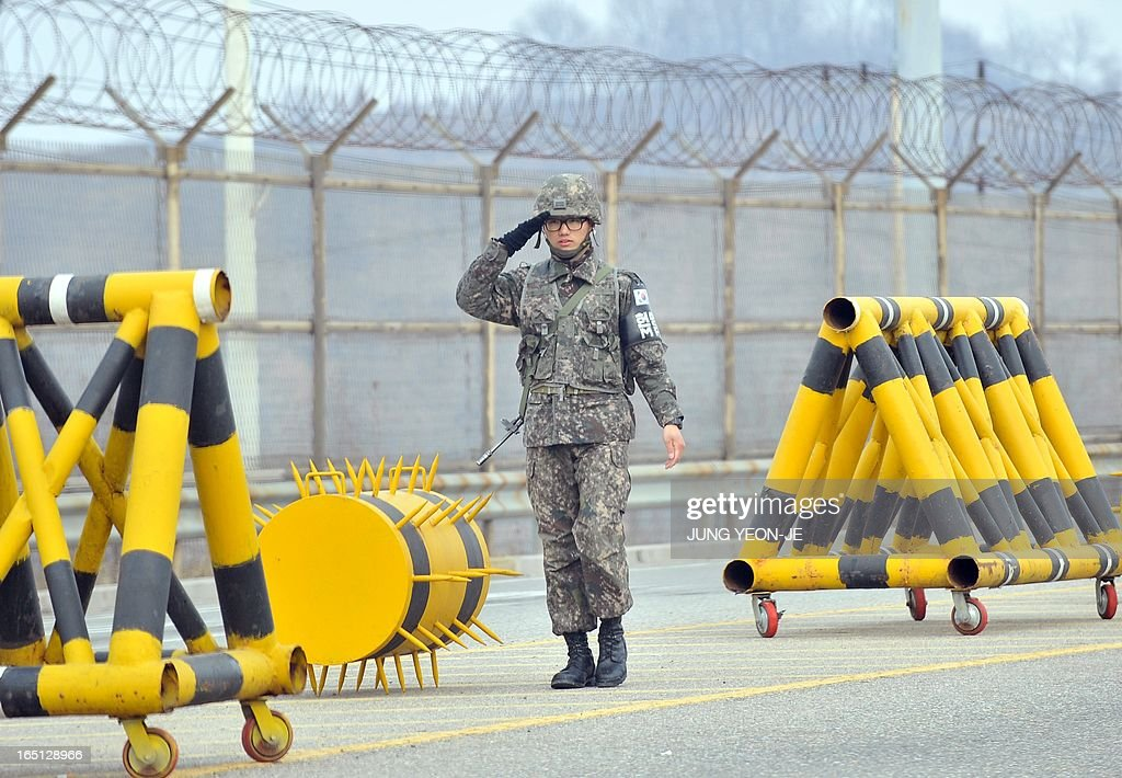 A South Korean soldier salutes next to barricades at a military check point on the road linked to North Korea in Paju near the Demilitarized Zone (DMZ) on April 1, 2013. South Korean workers and cargo on April 1 headed for the Kaesong Industrial Complex without a hitch despite North Korea's recent threat to close the joint industrial zone in the communist country.