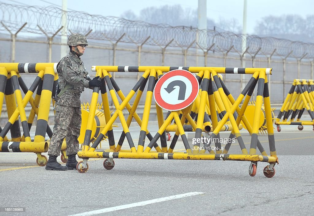 A South Korean soldier sets a barricade at a military check point on the road linked to North Korea in Paju near the Demilitarized Zone (DMZ) on April 1, 2013. South Korean workers and cargo on April 1 headed for the Kaesong Industrial Complex without a hitch despite North Korea's recent threat to close the joint industrial zone in the communist country.
