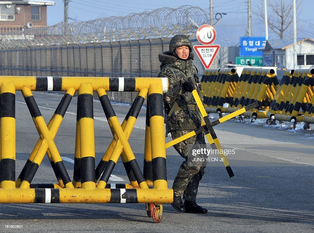 A South Korean soldier sets up barricades across the road linking North Korea's Kaesong Industrial Complex at a military check point in Paju near the demilitarized zone dividing the two Koreas on February 13, 2013. North Korea on February 12 staged its most powerful nuclear test yet and warned of 'stronger' action to follow if the ensuing wave of global condemnation translated into tougher sanctions.