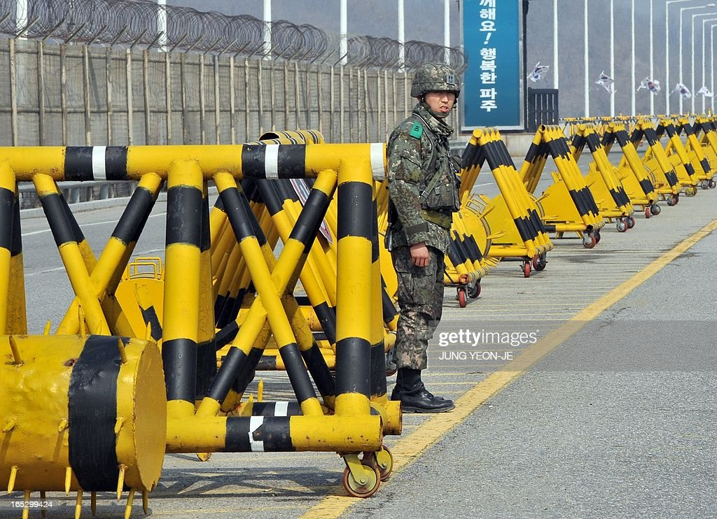 A South Korean soldier stands beside barricades on the road linked to North Korea at a military check point in Paju near the demilitarized zone (DMZ) dividing the two Koreas on April 3, 2013. North Korea on April 3 delayed the entry of South Koreans to a joint industrial complex in a rare move amid high tensions on the Korean peninsula, the South's Unification Ministry said.
